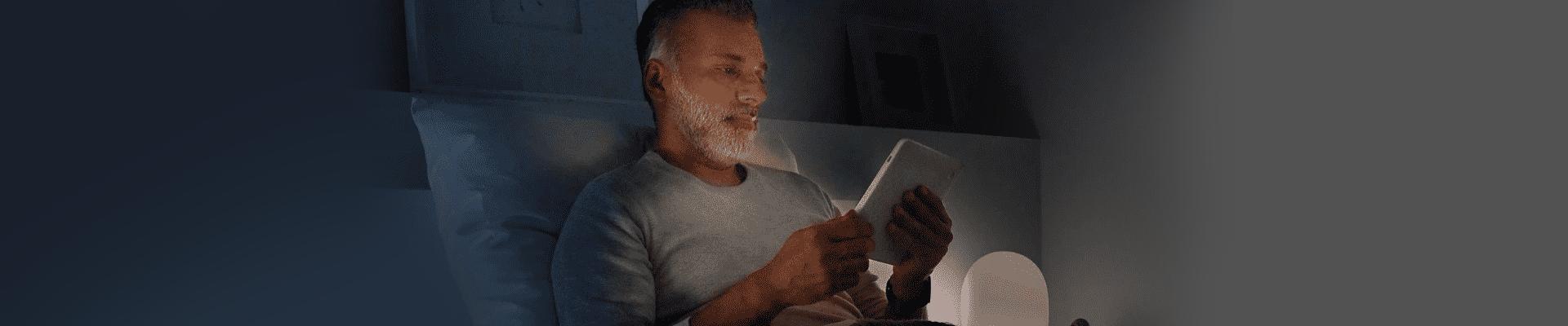 Man reading ebook on e-reader in dark